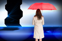 Businesswoman standing back to camera holding red umbrella Royalty Free Stock Photo
