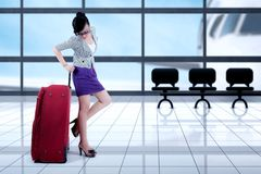 Businesswoman standing with baggage in the airport. Full length of pretty businesswoman wearing glasses while standing with baggage in the airport terminal Stock Images