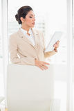 Businesswoman standing behind her chair holding tablet pc Royalty Free Stock Photography