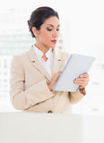 Businesswoman standing behind her chair using digital tablet Stock Image