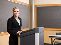 Businesswoman standing behind podium Royalty Free Stock Image