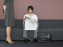 Businesswoman Standing By Businessman Reading Newspaper On Sofa royalty free stock photography