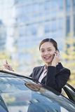 Businesswoman Standing by Car Using Phone, Looking At Camera Royalty Free Stock Photography