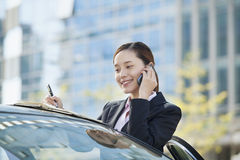 Businesswoman Standing by Car Using Phone, Reflection Stock Photo