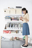Businesswoman Standing On Chair Reading Book. Full length of young businesswoman standing on chair reading book by shelves Stock Image