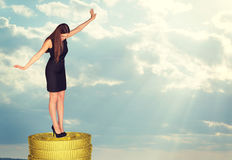 Businesswoman standing on coins stack in balance Royalty Free Stock Photography