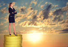 Businesswoman standing on coins stack Royalty Free Stock Image