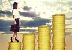 Businesswoman standing on coins steps Stock Photos
