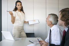 Businesswoman standing beside conference table in meeting room, talking to male colleagues Stock Images