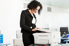 Businesswoman standing at the copying machine Stock Photography