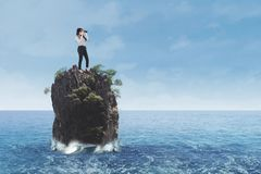 Businesswoman standing on coral reef at sea. Young businesswoman standing on coral reef at sea while looking through binoculars stock photography
