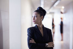 Businesswoman standing in the corridor with arms crossed looking away Stock Photos