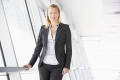 Businesswoman standing in corridor smiling Royalty Free Stock Photo
