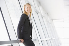 Businesswoman standing in corridor smiling royalty free stock photography