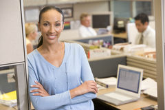 Businesswoman standing in cubicle smiling stock photo