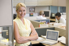 Businesswoman standing in cubicle smiling Stock Image