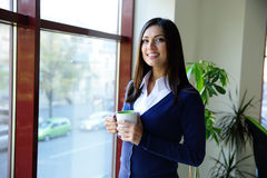 Businesswoman standing with cup of coffee Royalty Free Stock Photography