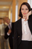Businesswoman standing on door while businessman standing in background Royalty Free Stock Images