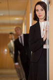 Businesswoman standing on door while businessman standing in background Royalty Free Stock Image