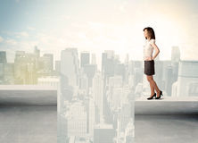 Businesswoman standing on the edge of rooftop Stock Photo