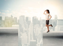 Businesswoman standing on the edge of rooftop Royalty Free Stock Photo