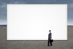 Businesswoman standing at empty billboard Stock Photos