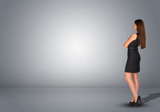 Businesswoman standing in an empty gray room. Rear Stock Photos