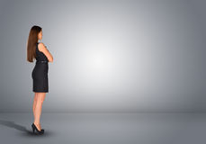 Businesswoman standing in an empty gray room. Rear Stock Images