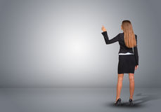 Businesswoman standing in an empty gray room. Rear Royalty Free Stock Photo
