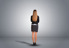 Businesswoman standing in an empty gray room. Rear Royalty Free Stock Image