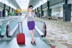 Businesswoman standing on escalator Stock Photos