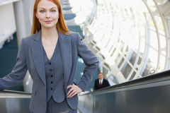 Businesswoman standing on escalator, hand on hip, smiling, front view, portrait, elevated view Royalty Free Stock Photo