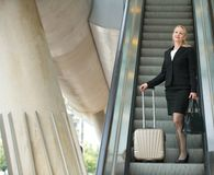 Businesswoman standing on escalator with luggage Stock Images