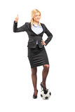 Businesswoman standing on a football Stock Image