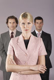 Businesswoman Standing In Front Of Businessmen Stock Photo