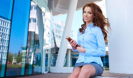 Businesswoman standing in front of office buildings Royalty Free Stock Photos