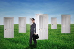 Businesswoman standing in front of opportunity doors. Confident businesswoman standing in front of opportunity doors on the green field Royalty Free Stock Photos