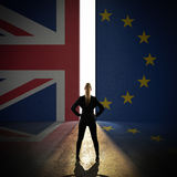 Businesswoman standing in front of a wall with the union jack and the eu flag. And a portal Stock Images