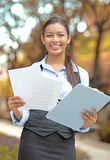 Businesswoman standing holding company documents. Closeup portrait happy young businesswoman standing holding company documents papers contract  on outside Stock Image