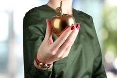 Businesswoman  standing  and holding golden  apple in her hand. Stock Photography