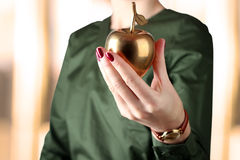 Businesswoman  standing  and holding golden  apple in her  hand. Stock Photo