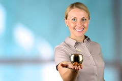 Businesswoman  standing  and holding golden  apple in her  hand. Royalty Free Stock Photography