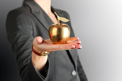 Businesswoman standing and holding golden apple in her hand. Royalty Free Stock Image
