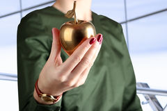 Businesswoman  standing  and holding golden  apple in his hand. Royalty Free Stock Photography