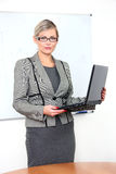 Businesswoman standing and holding laptop Stock Photo