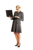 Businesswoman standing and holding a laptop Royalty Free Stock Photos