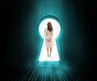 Businesswoman standing in keyhole door Stock Image