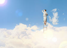 Businesswoman standing on ladder Royalty Free Stock Photography