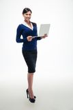 Businesswoman standing with laptop and looking at camera Stock Photography