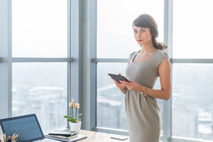 Businesswoman standing in loft light room, typing, reading e-mail, browsing information on-line, using applications her stock images